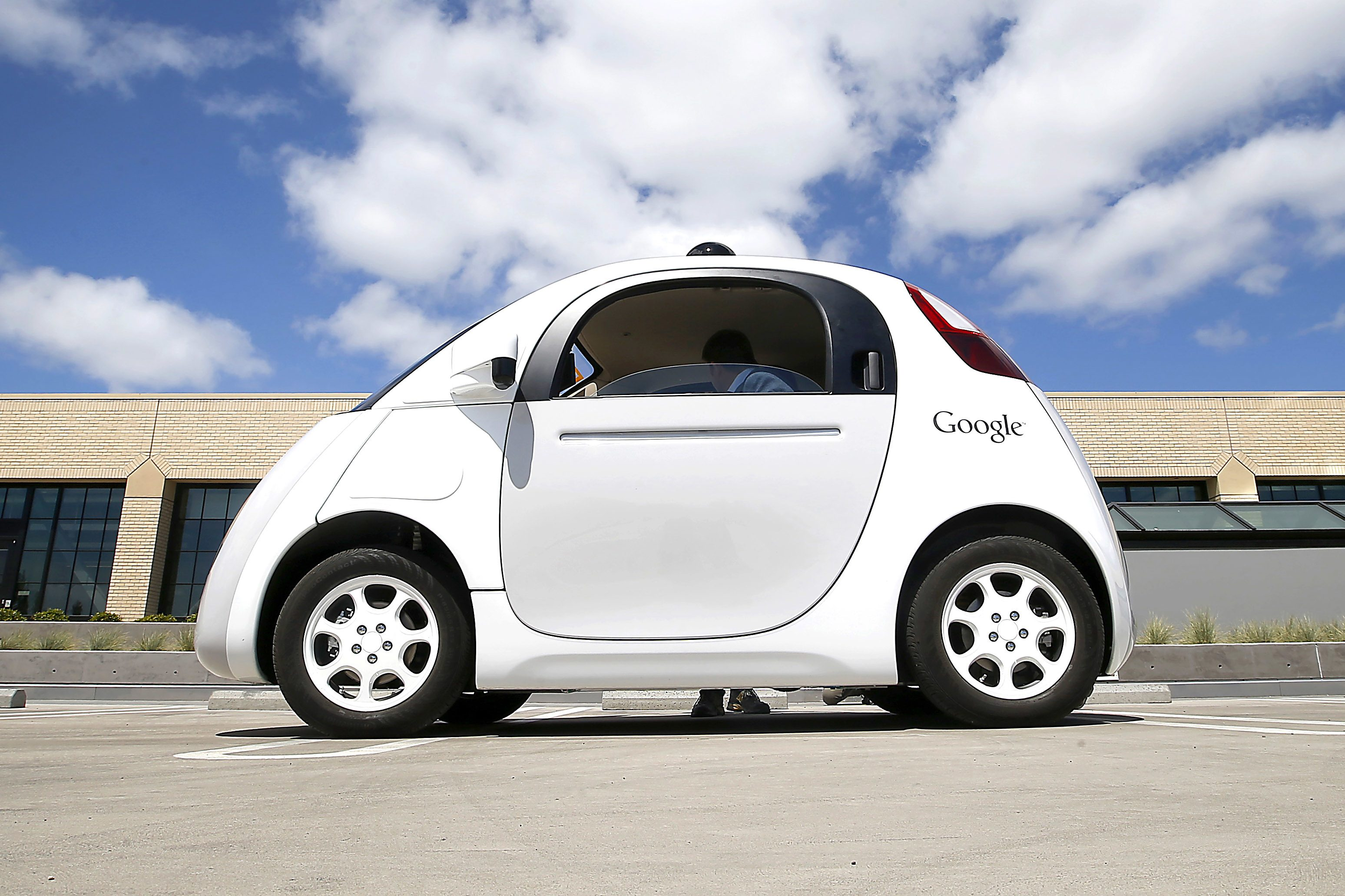 In this May 13, 2015 photo, Google's new self-driving prototype car is presented during a demonstration at the Google campus in Mountain View, Calif.  The car, which needs no gas pedal or steering wheel, will make its debut on public roads this summer. (AP Photo/Tony Avelar)